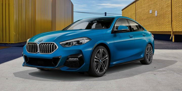 A blue metallic 2020 BMW 228i xDrive Gran Coupe parked between yellow buildings.