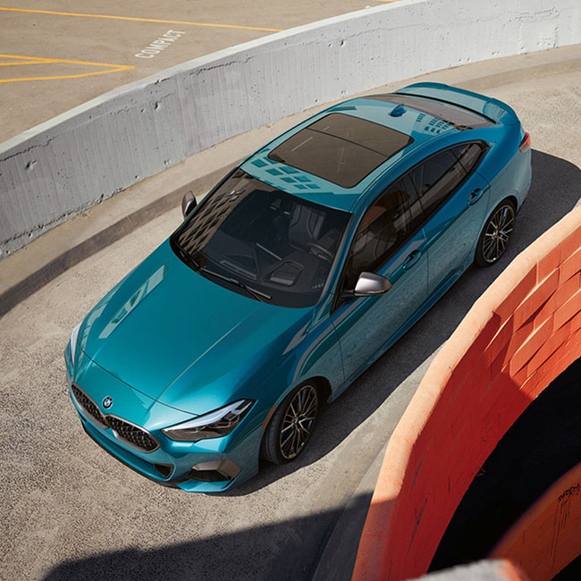 A blue metallic BMW 2 Series Gran Coupe driving down parking garage ramp.