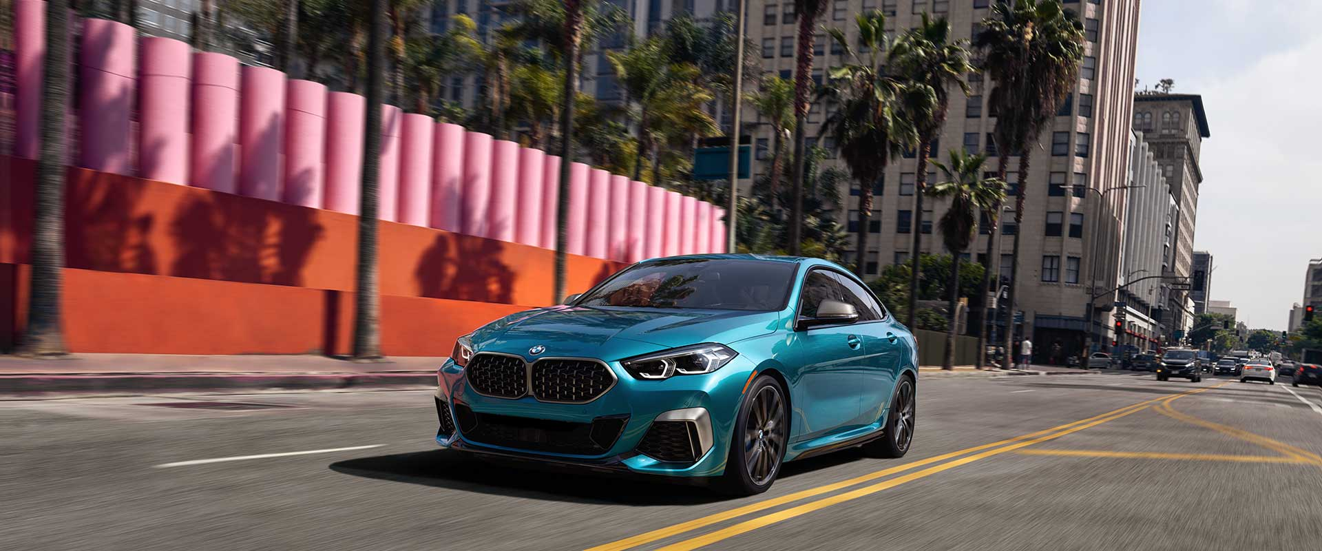 A blue metallic BMW 2 Series Gran Coupe driving down street during the day.