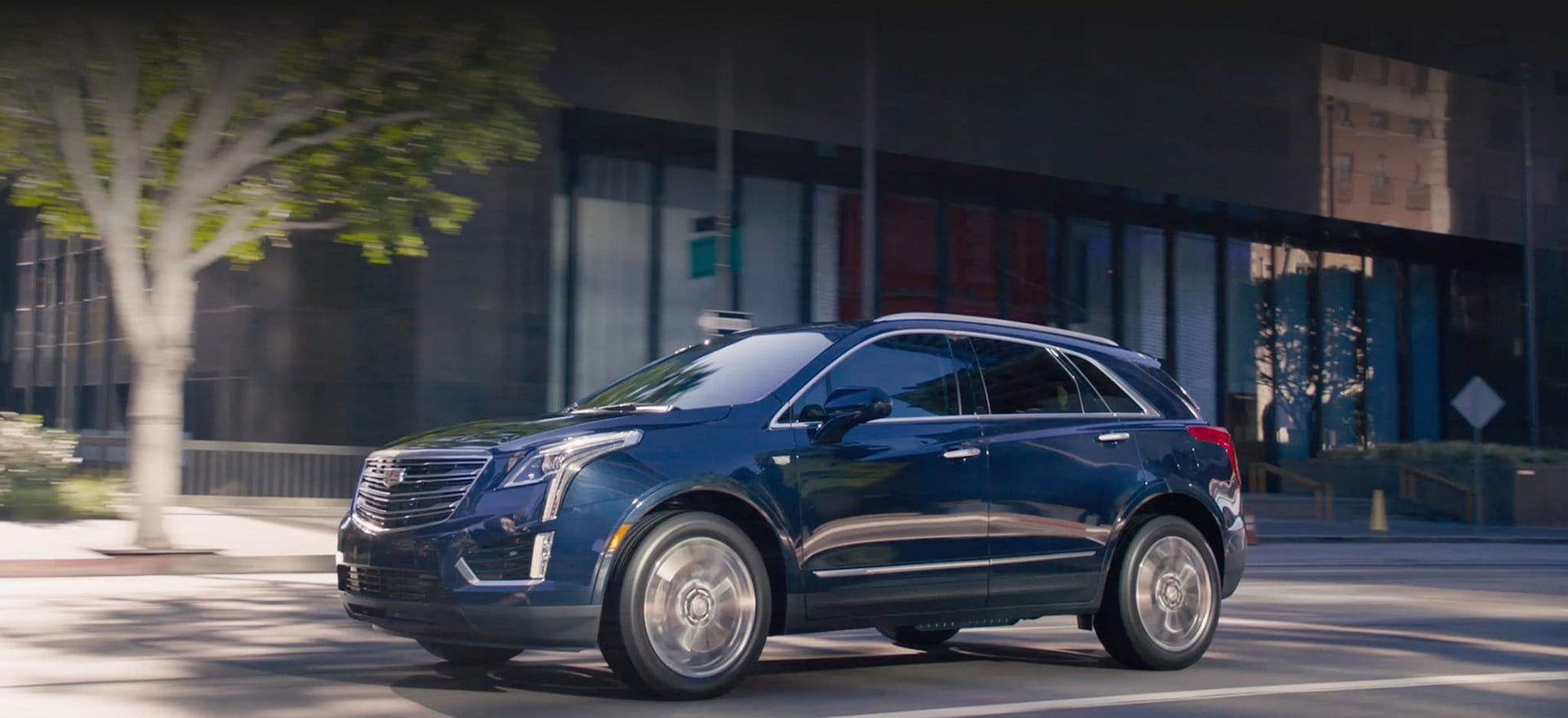Cadillac SUV driving on a city street