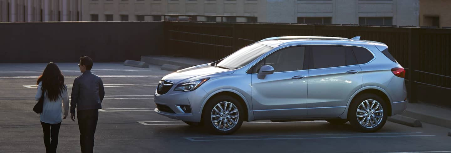 2019 Buick Envision in a parking lot with a couple walking towards it