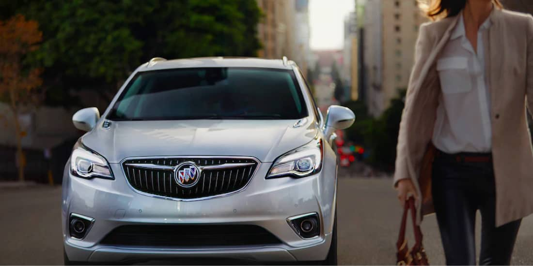 a silver Buick Envision front view with a woman walking in front