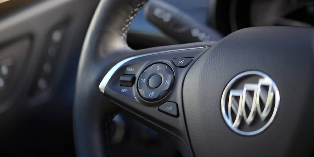 A Buick Envision's steering wheel with cruise control buttons