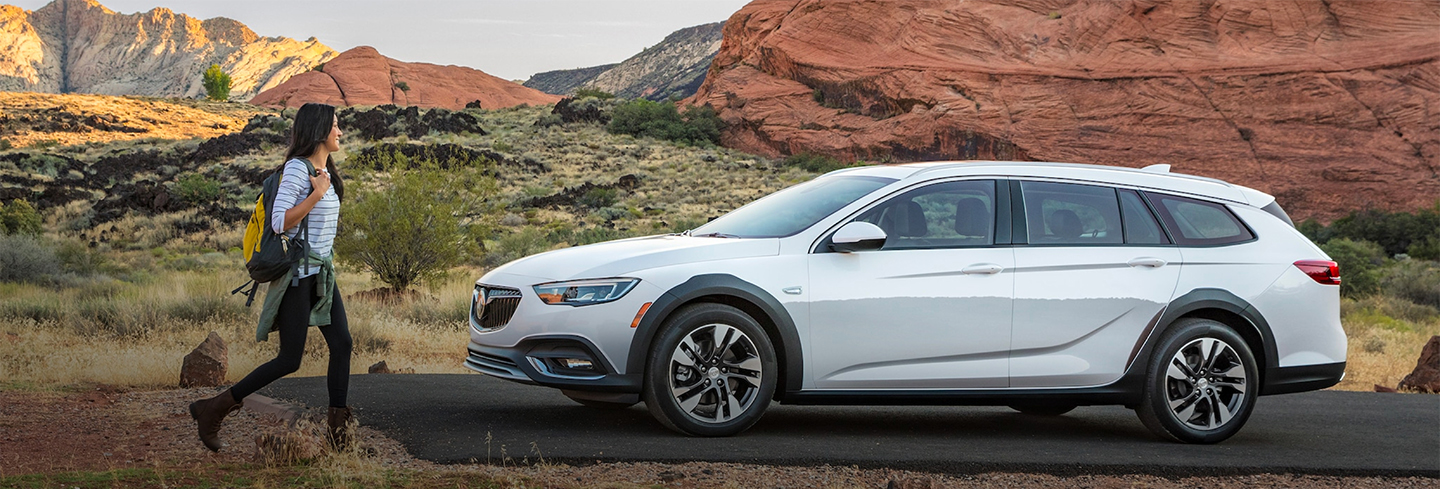 2019 White Buick Regal TourX Sideview Parked with Woman Walking to the Car
