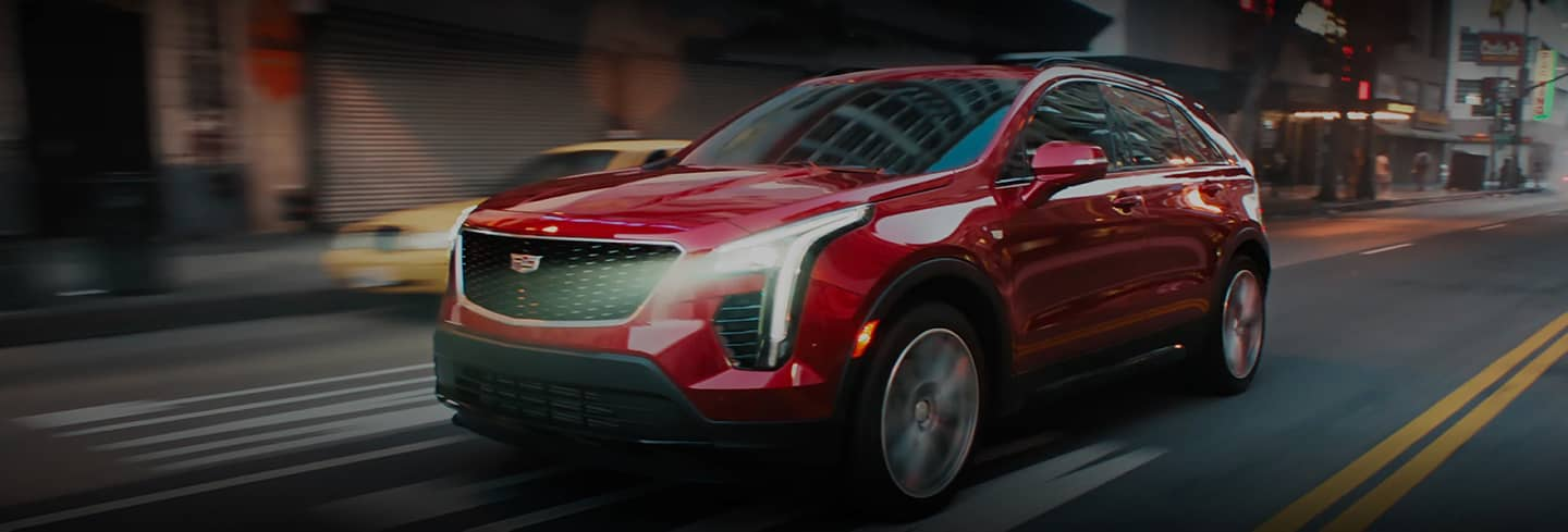 2020 Red Cadillac XT4 Driving Down City Street