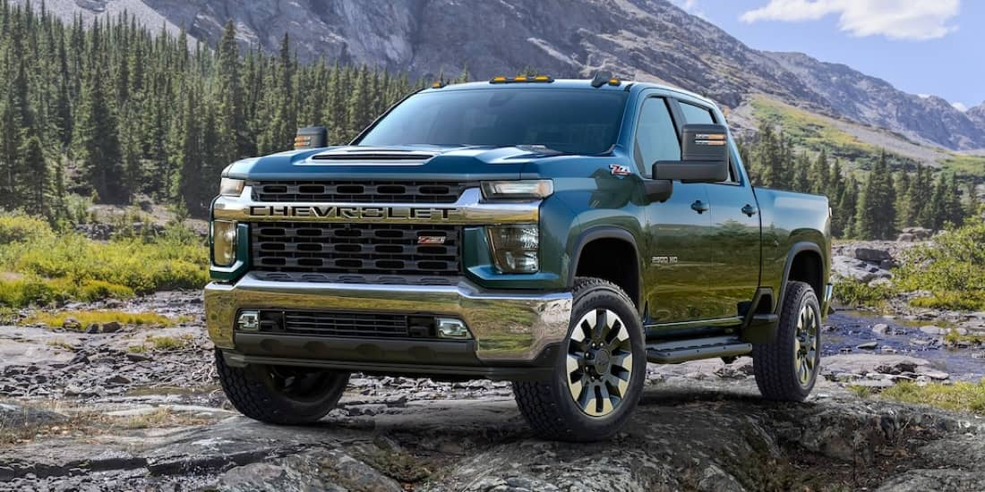 Front facing of a blue Chevrolet Silverado HD with mountains in the background