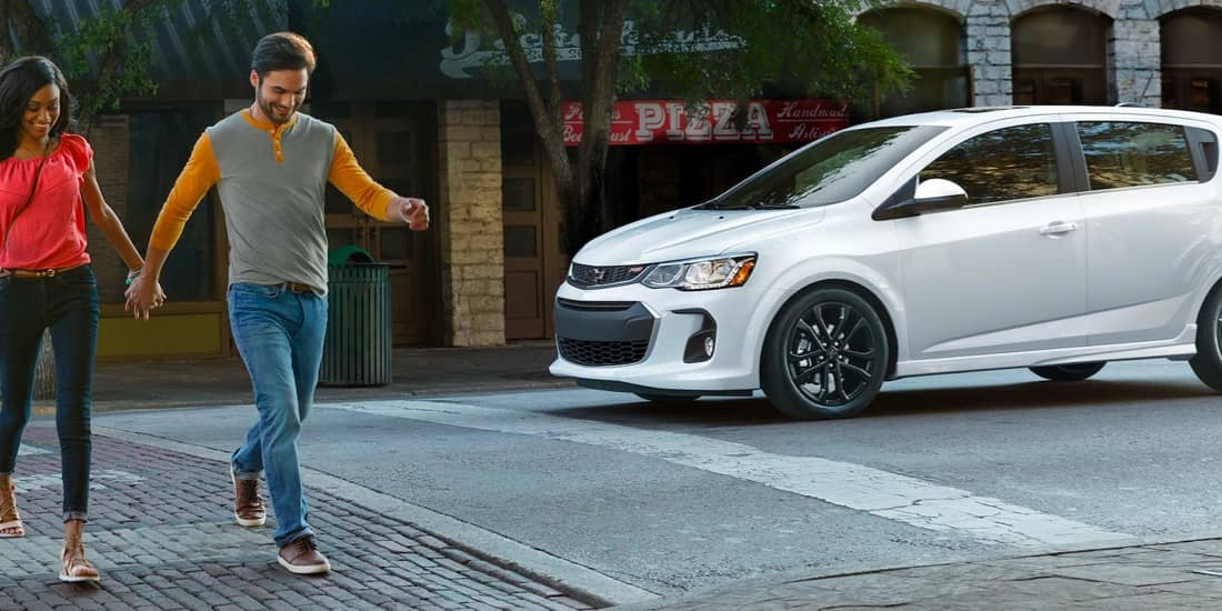 White Chevy Sonic stopped at a crosswalk