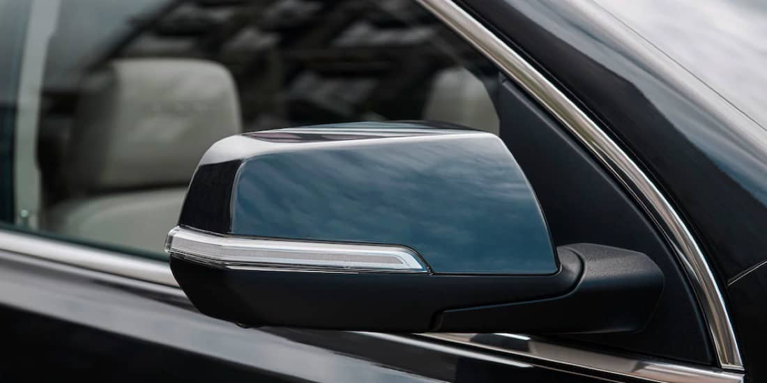 A blue Acadia's sideview mirror