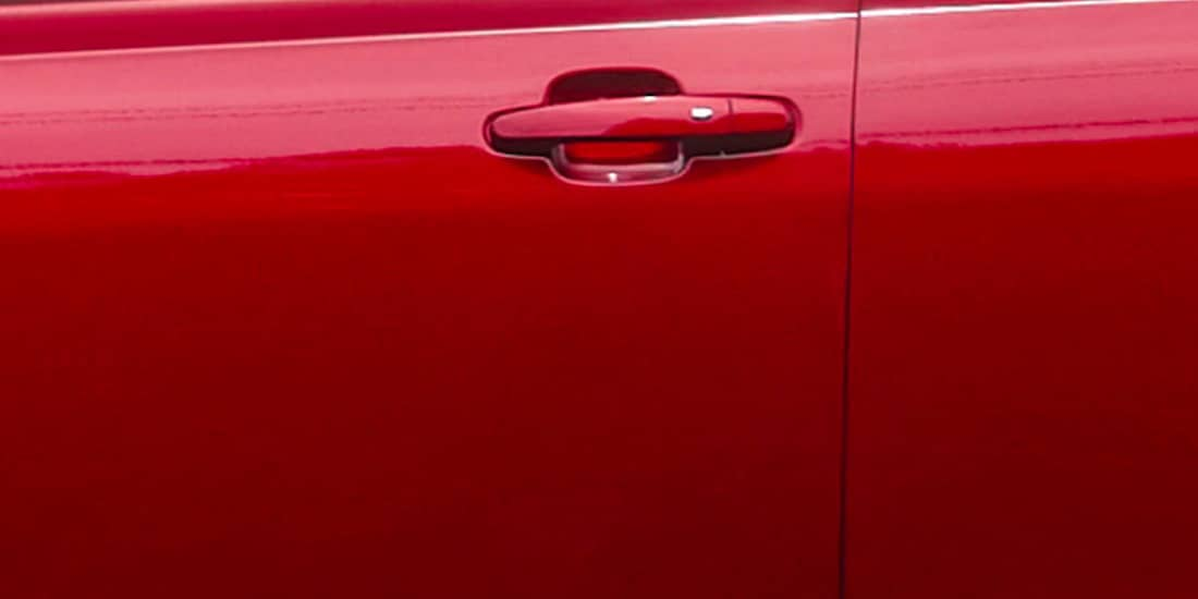 A red Acadia's outside door handle