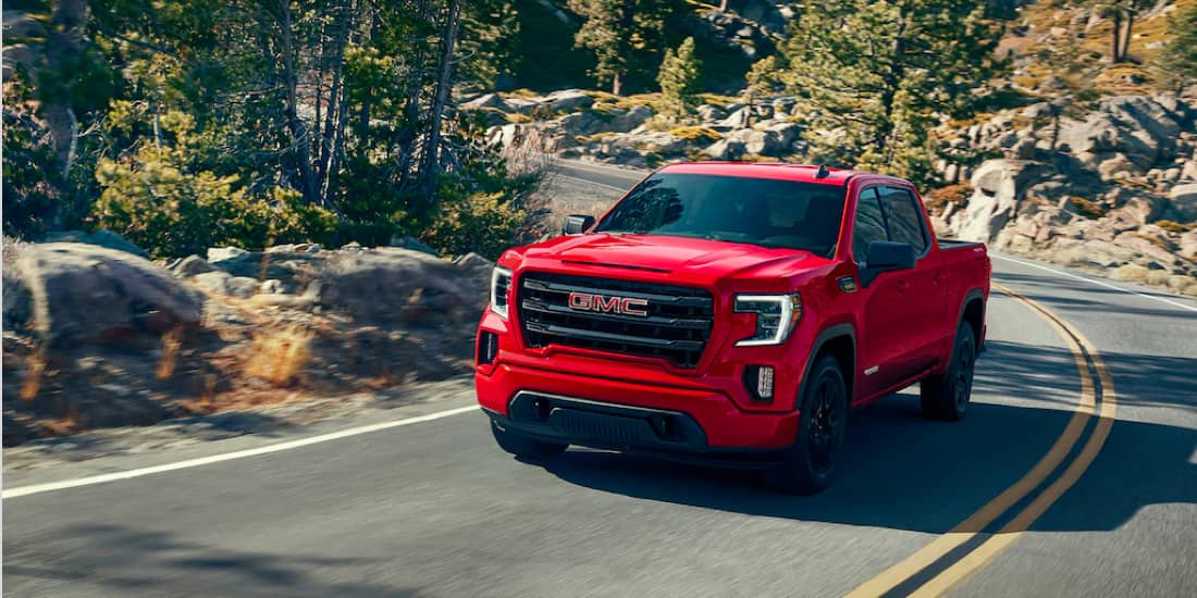 Cardinal red GMC Sierra 1500 turning through a mountainside