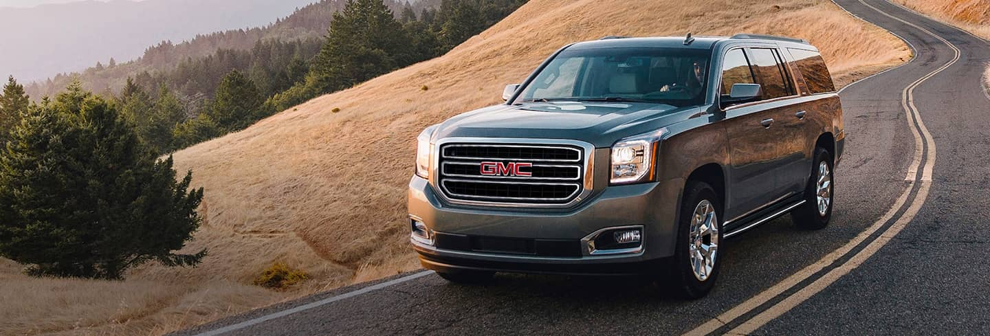 2020 Gmc Yukon Angled View Driving Down a Country Road