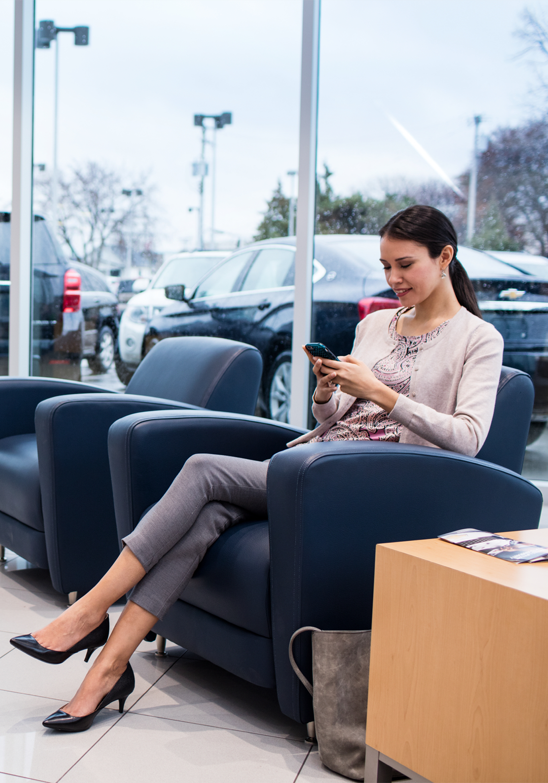 Woman on phone sitting in dealership