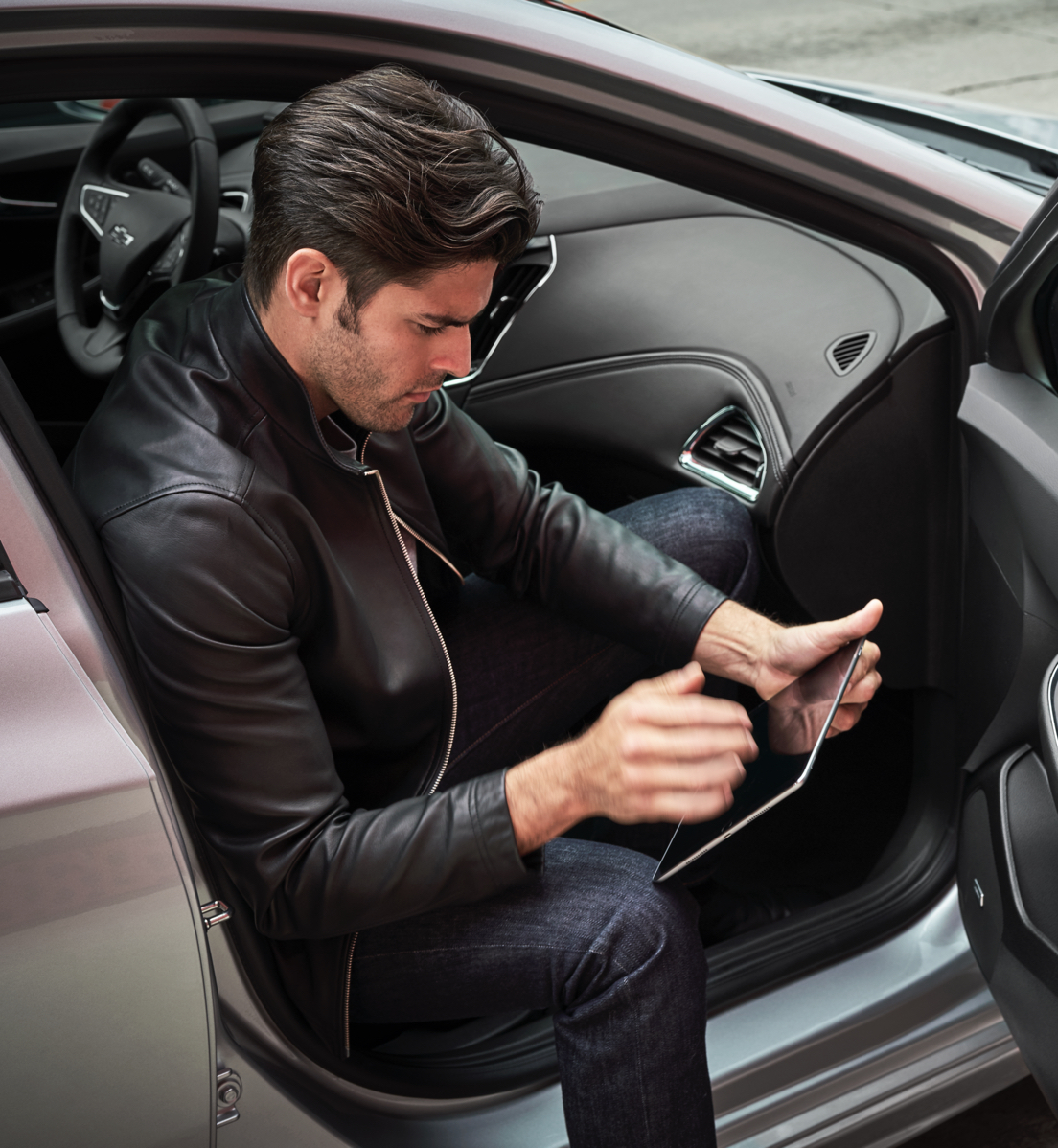 Man on tablet sitting in car