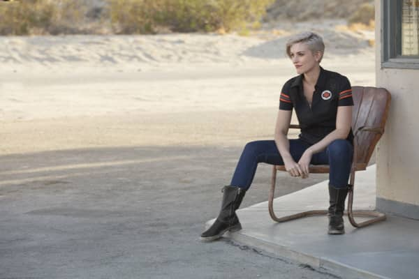 A women with short blond hair sitting in a chair wearing a black V-neck polo from the Harley-Davidson Genuine MotorClothes collection.