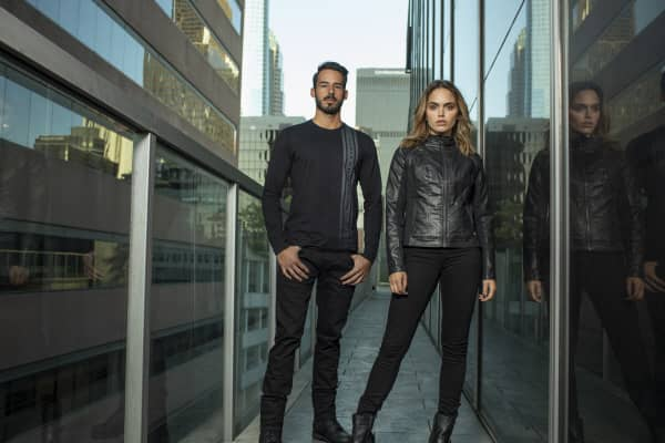 A young modern looking man and women wear sleek black clothes from the Harley-Davidson H-D Moto Collection.