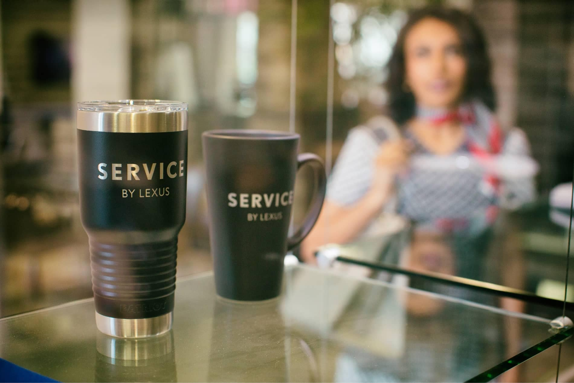 Close up of coffee mugs with Service by Lexus printed on them.