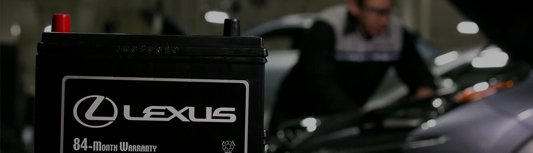 A close up of a Lexus battery with a Service Technician looking in the hood of a car in the background.
