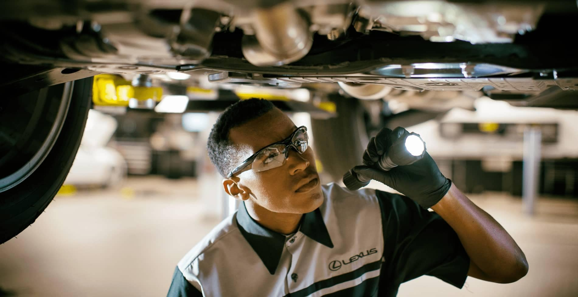 A Service Technician looking at the underneath of a car with a flashlight.