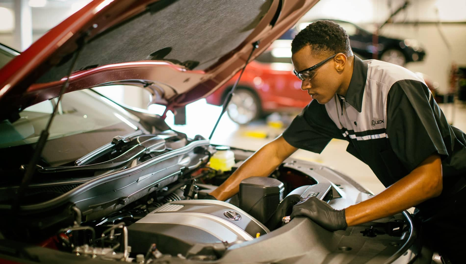 Service Technician reaching into the front of a car.