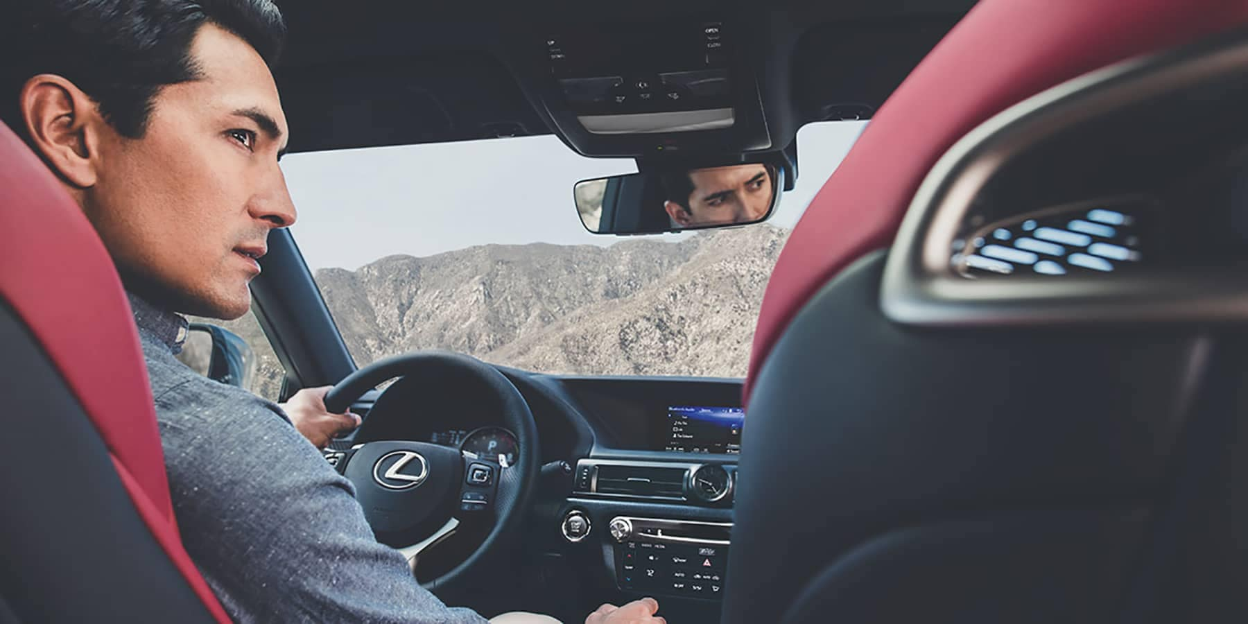 Inside view from the backseat of a man driving a Lexus.