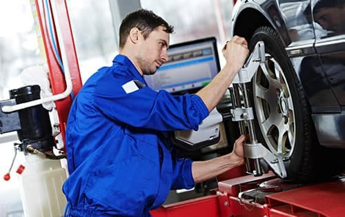 Service Technician in the process of aligning a wheel.