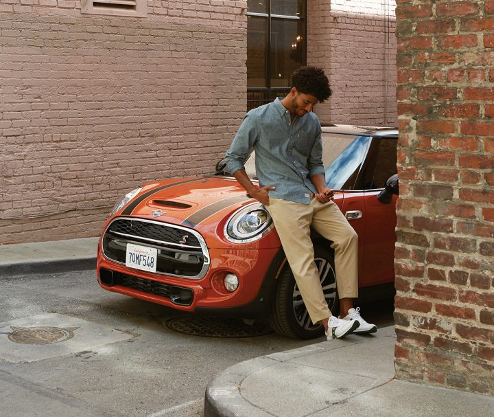 Young man sitting on the hood of a MINI.