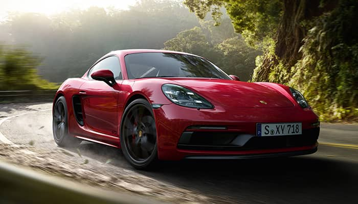 Red Porsche driving on a road through a lush green forest.