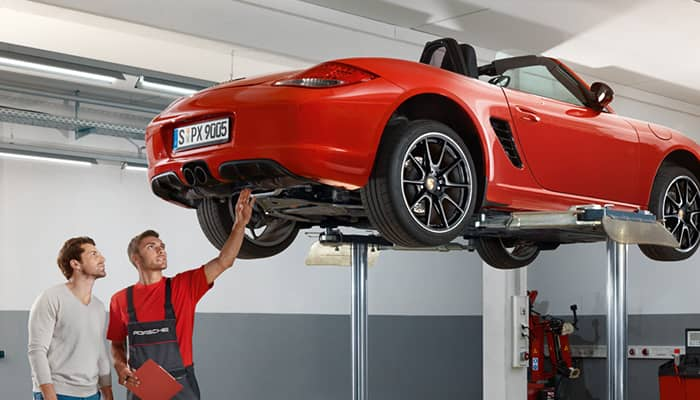 Red Porsche on a service lift being inspected by two technicians.