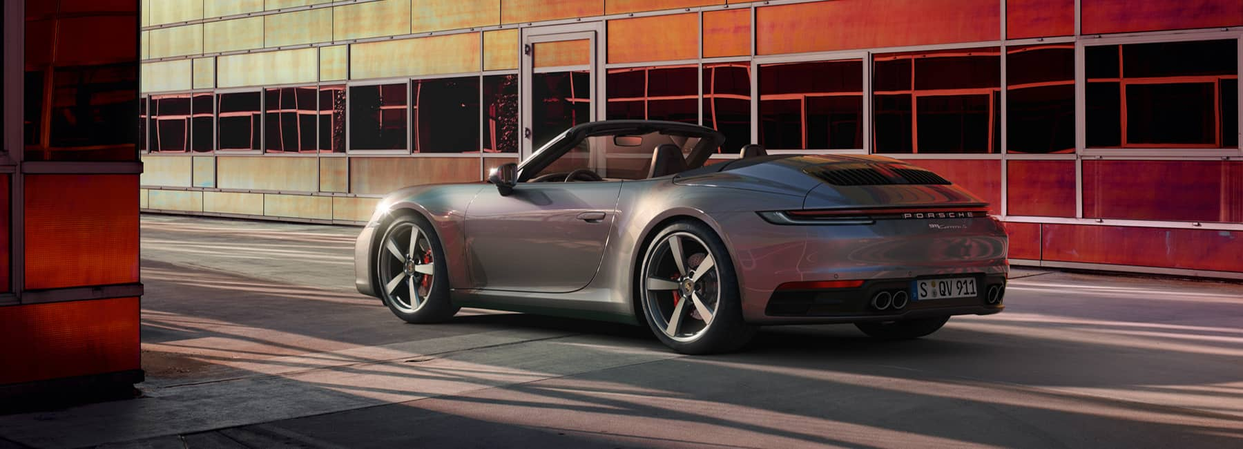 A grey Porsche convertible parked in front of a warehouse.