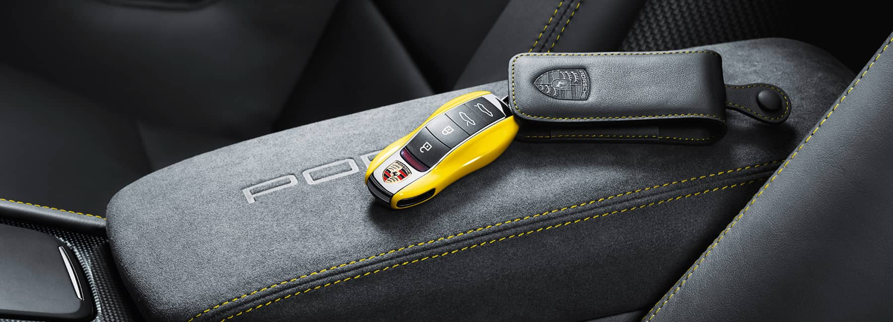 A yellow Porsche key fob resting on the center arm rest inside a vehicle.