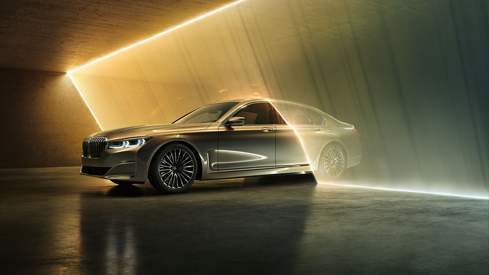 A BMW 7 Series driving through a sheet of falling water in a garage.